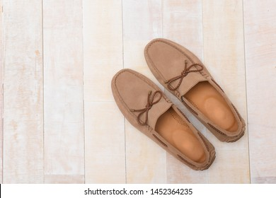 Men's brown loafers isolated on wooden  background.