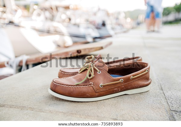 Mens brown loafers shoe on a pier head for Yacht Marina