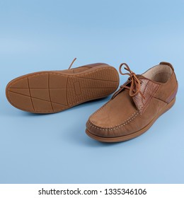 Men's brown moccasins, loafers isolated on blue background. Side view, top. Brown topsiders