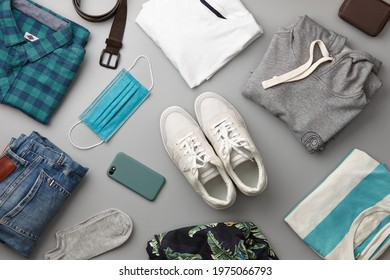Mens casual clothing outfits and accessories flat lay on gray background, top view