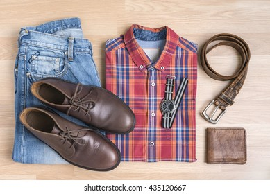 Men's casual outfits with accessories on wooden table, red blue cotton plaid shirt,  jeans pants, watch, brown shoes, wallet and belt, trendy fashion,  top view