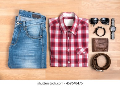 Men's casual outfits with accessories on wooden table, Red plaid shirt and blue jeans with eyeglasses, bracelet, wallet, brown belt and watch, top view