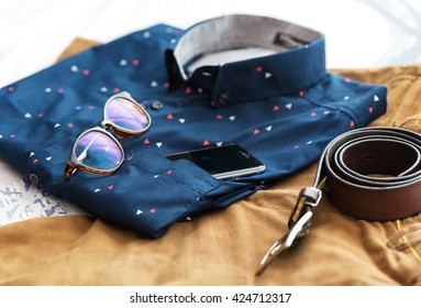 Men's casual outfits background, Blue shirt, brown short pants, brown belt, glass and smart phone.