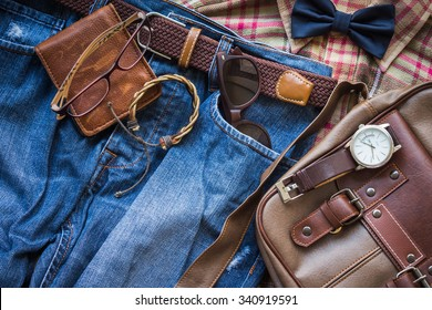 Men's casual outfits background, brown plaid shirt, bow tie, blue jeans, brown bag and stationary