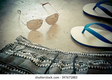 Men's casual outfits for the beach on cement grunge background,
