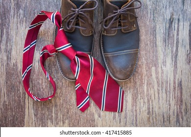 Men's casual outfits with brown shoes and red necktie on rustic wooden background, father's day concept