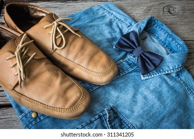 Men's casual outfits with jeans shirt, bow tie and brown shoes on wooden background