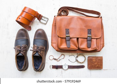 Men's casual outfits with leather accessories on white rustic wooden background, lifestyle traveler, beauty and fashion concept