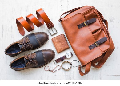Men's casual outfits with leather accessories on white rustic wooden background, beauty and fashion concept