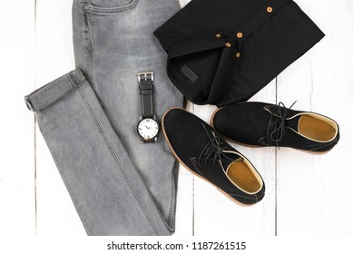 Men's casual outfits for man clothing set with black ankle boot , watch, gray jeans and office shirt isolated on white background, Top view