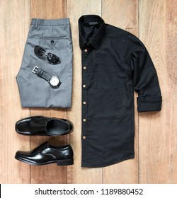 Men's casual outfits for man clothing set with office shoes , watch, trousers, black shirt,  and sunglasses on wooden background, Top view