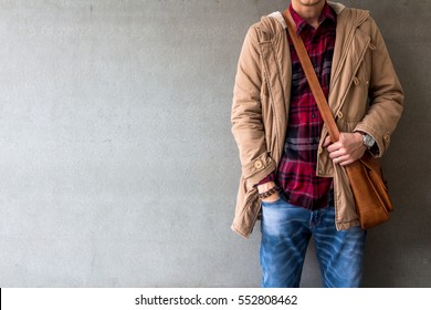 Men's casual outfits wear blue jeans with red plaid shirt, brown coat and leather bag standing over gray grunge background with space, lifestyle traveler, beauty and fashion concept