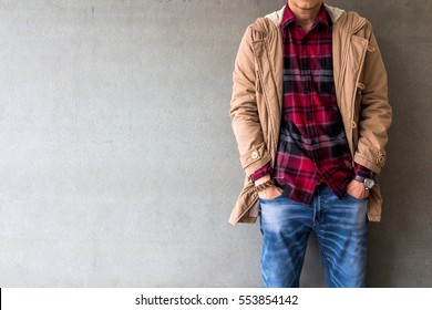 Men's casual outfits wear blue jeans with red plaid shirt and brown coat standing over gray grunge background with space, lifestyle traveler, beauty and fashion concept