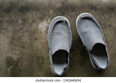Men's casual shoes that have been removed on concrete floor.