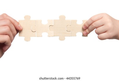 mens and childs hands holding set of puzzles