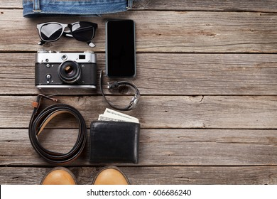 Men's clothes and accessories. Jeans, shoes, glasses, camera, smartphone on wooden background. Top view with copy space