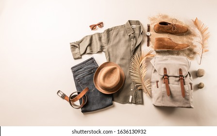 Men's clothing and accessories - khaki linen shirt, camel desert shoes, jeans, straw hat and backpack. Classic casual fashion outfit for tourist or traveler captured from above (top view, flat lay).