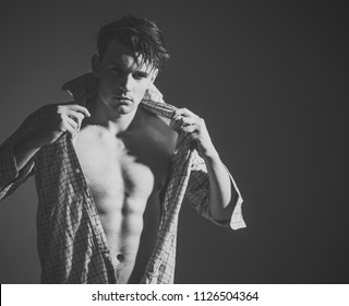 Men's Clothing. Masculine concept. Guy looks confident and attractive. Man with torso, muscular macho with six packs, dressing shirt, dark background. Macho on pensive face, muscular figure, sportsman