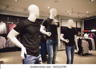 Men's clothing store. Three mannequin dressed in black t-shirts in clothing store.
