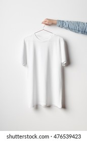 Men's Crew Neck T-Shirt Mock-Up - Man holding a white t-shirt on a copper wire clothes hanger