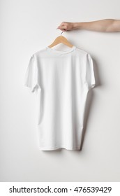 Men's Crew Neck T-Shirt Mock-Up - Man holding a white t-shirt on a wooden clothes hanger. Backside