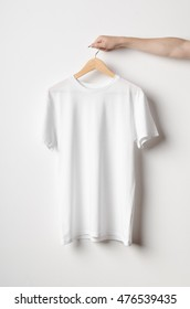 Men's Crew Neck T-Shirt Mock-Up - Man holding a white t-shirt on a wooden clothes hanger