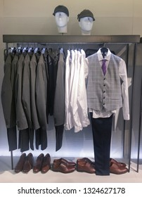 Men's ,different suits with shirts, shoes, handbag in shop