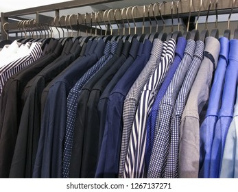Men's different suits with shirts and ties in clothing store