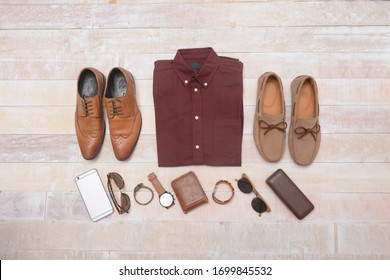 Men's fashion brown shirts and accessories on wooden background, flat lay