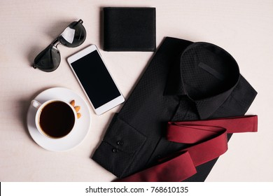 Men's fashion clothing with several accessories glasses, mobile phone, black leather walet and cup of hot coffee, on white background, top view.