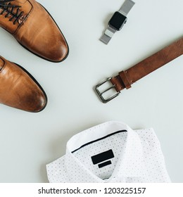 Men's fashion composition with watch, shirt, belt and shoes. Flat lay, top view.