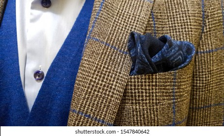 Men's fashion concept with a blue pocket square with a brown checkered suit with blue details, with a blue cashmere sweater vest underneath and a light blue shirt