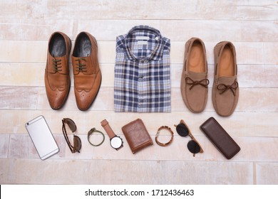 Men's fashion plaid shirts and accessories on wooden background, flat lay