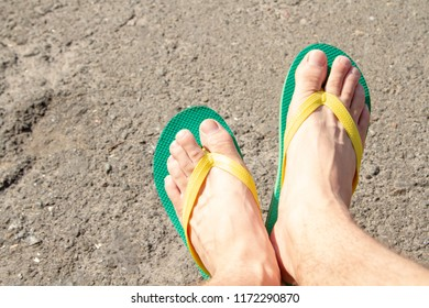 Men's feet in green slaps with yellow elastic bands. Summer outdoor men's shoes. Men's beach slaps against the background of asphalt.