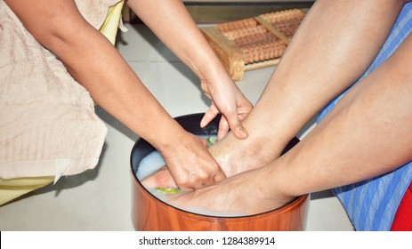 Men's feet are immersed in herbal water in a circular wooden tub, foot spa to relax before Thai massage.