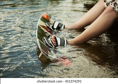 Men's feet on a wakeboard in water.guy sitting by the river and is preparing to go wake boarding