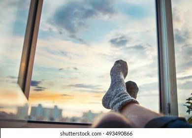 Men's feet in socks on relaxation window