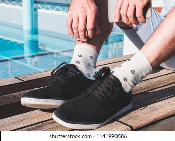 Men's feet in sport shoes and white socks with a sea pattern in the form of anchors on the open deck of a cruise liner against the background of the pool and the sea