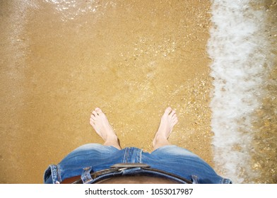 men's feet in the water on the beach.the view from the top