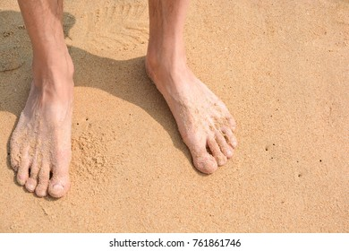 Men's feet in the yellow sand on the beach