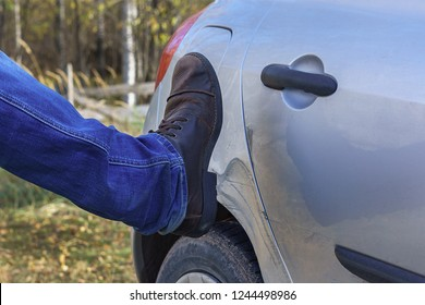 Men's foot in jeans and in a brown boot kicks the car