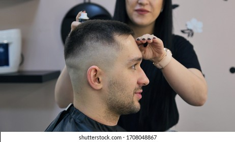 Men's hairstyle and haircut at the hairdresser. Hair care. Barbershop. Woman hairdresser doing hairstyle to adult man. Workplace hairdresser