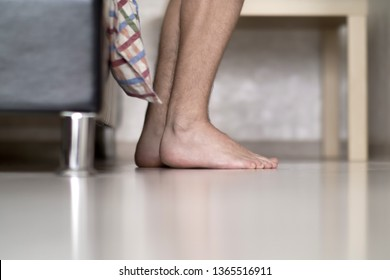 Men's hairy legs next to the bed