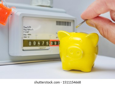 Men's hand with coin and yellow piggy bank near a gas meter at home. Symbolic image of cost, energy efficiency and saving natural gas at home.