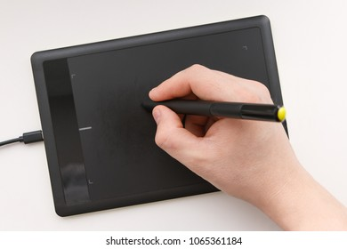Men's hand draws on a graphics tablet using a stylus