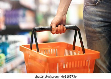 Men's hand holding an empty basket in the supermarket. Grocery shopping concept.