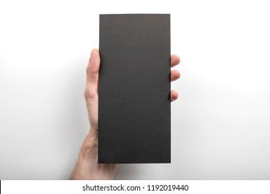 Mens hand holding empty black flyer on white background. Blank paper mock-up