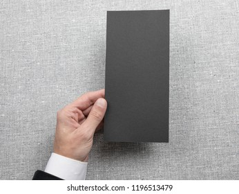 Mens hand holding empty black flyer on light gray background. Blank paper mock-up