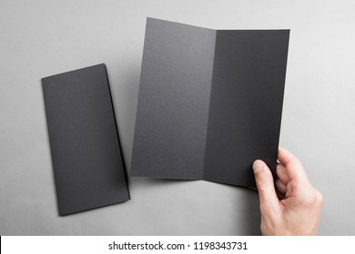 Mens hand holding empty black booklet on gray background. View from above