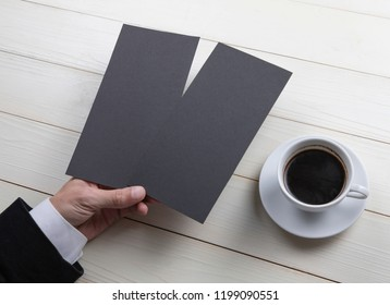 Mens hand holding empty black flyers on wooden background. Blank paper mock-up